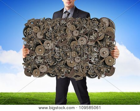 Businessman holding gears mechanism as teamwork concept