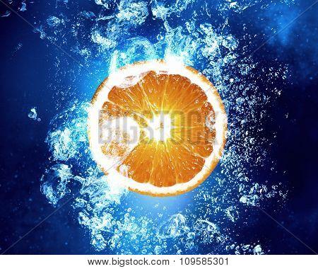 Orange fruit in clear blue water splashes