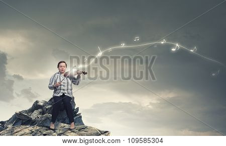 Middle aged stout woman sitting on stone and playing violin