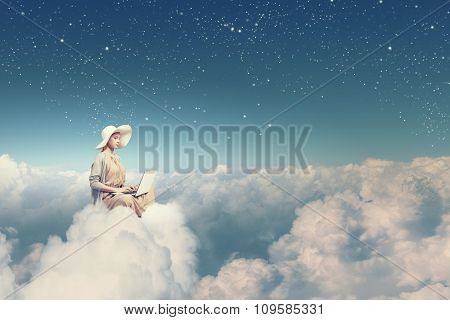 Woman in dress and hat sitting on cloud and working on laptop