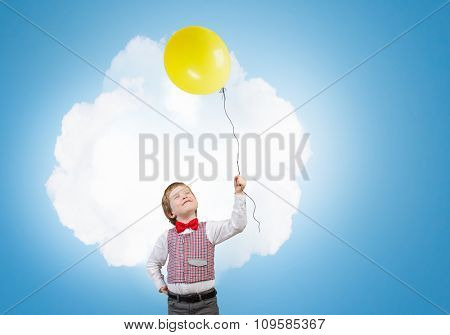 Little boy wearing red bowtie holding colorful balloon