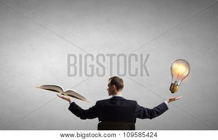 Young businessman with book in one hand and bulb in other