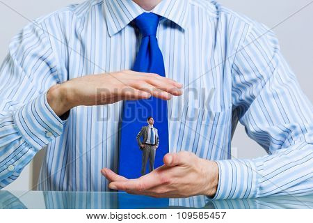 Miniature of businessman in palm protected with care