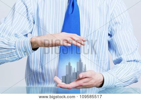 Close up of hands holding image of modern cityscape