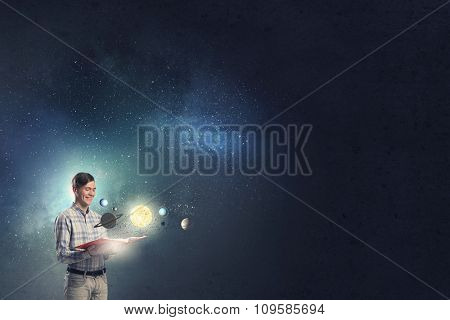 Young man with book and planets of space spinning around