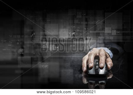 Hand of businessman in suit on dark digital background using wireless computer mouse