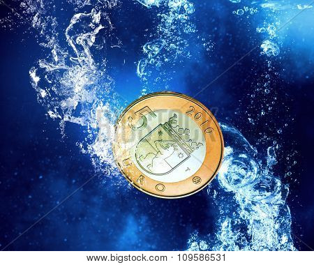 Five euro coin in clear blue water