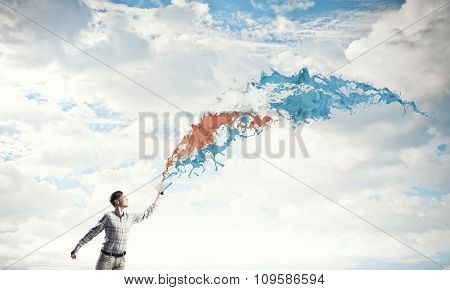 Young handsome man reaching hand with book and colorful splashes flying out of pages