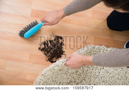 Hands Cleaning Mud On Hardwood Floor At Home