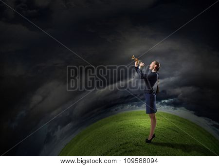 Young pretty businesswoman playing melody on trumpet