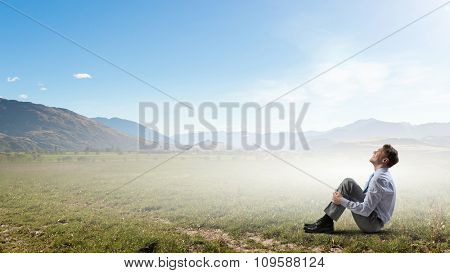 Young businessman sitting alone on grass in park