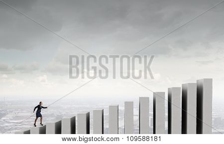 Determined businesswoman running upward business graph bar