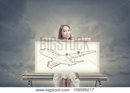 Unrecognizable woman showing white banner with airplane design