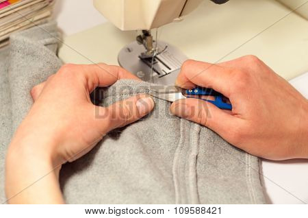 Woman's Hands With Scissors Cut The Thread After Sewing On The Sewing Machine