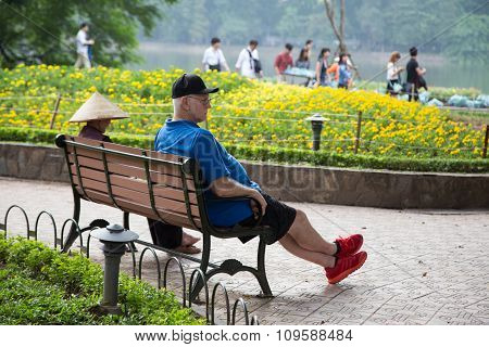 Foreign visitor taking a rest on a wooden bench next to a local Asian woman