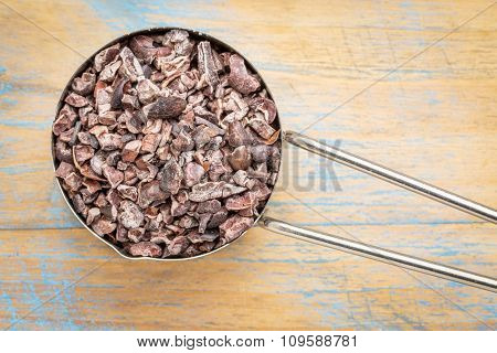 Raw cacao nibs in a metal measuring scoop against painted wooden background