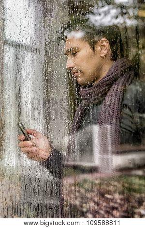 Man With Phone Behind Wet Window