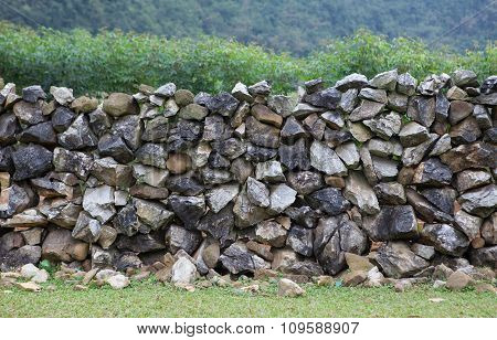 Stone wall on a hill with grass field