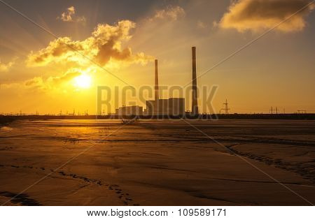 Thermal Power Plant On The Banks Of A Dried-up Pond On The Sunrise Background
