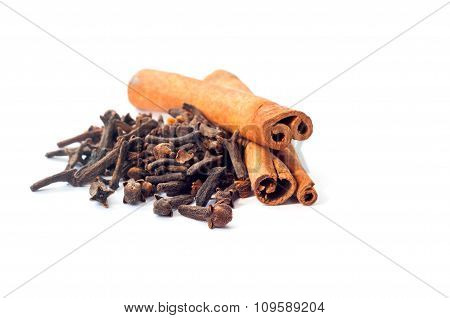 Two cinnamon sticks and a pile of dried cloves cloves on a white background