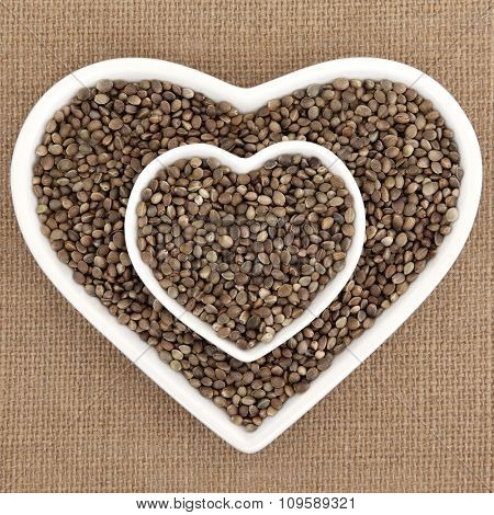 Hemp seed health food in heart shaped porcelain bowls over hessian background.