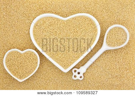 Couscous in heart shaped bowls and porcelain spoon forming an abstract background.
