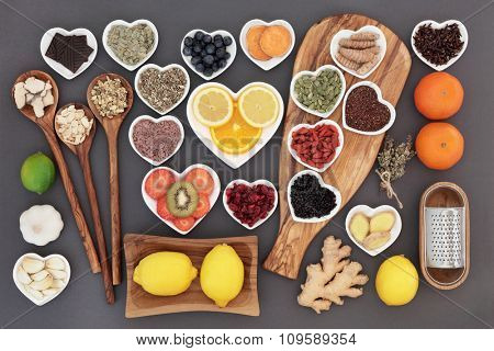 Super food and herb selection for cold and flu remedy including foods high in antioxidants and vitamin c over grey background.