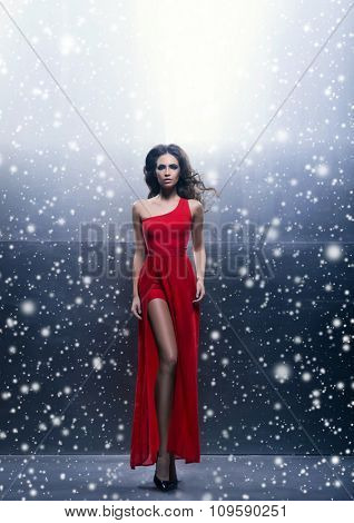 Young, beautiful and passionate woman in a wavy, long, red dress over winter background.