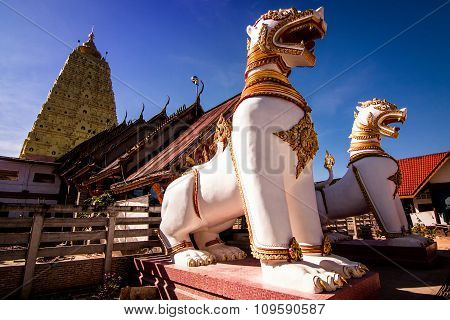 Two White Lion Statue In Front Of A Golden Stupa.