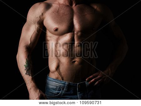 Torso of young muscular man wearing jeans