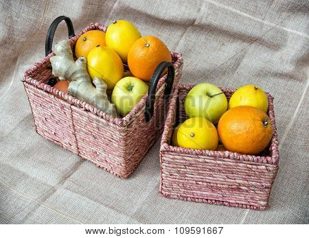 Two Wicker Baskets With Apples, Oranges, Lemons And Ginger