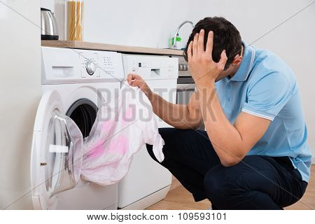 Tensed Man Holding Dirty Tshirt By Washing Machine