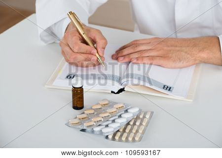 Doctor Writing Prescription At Table In Clinic