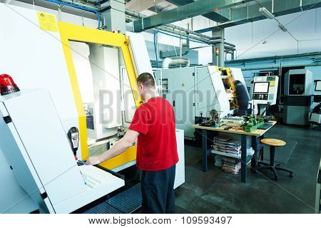 mechanical industrial worker at cnc milling machine center in tool manufacture workshop. Authentic shooting in challenging conditions.