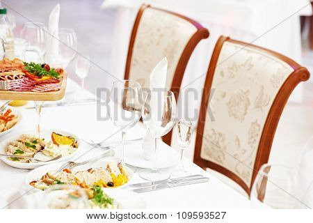 catering table set service with silverware, glass stemware and napkin at restaurant before party