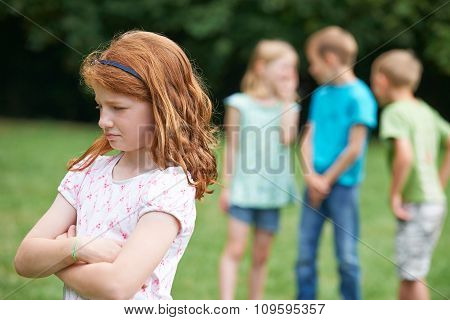 Unhappy Girl Being Gossiped About By Other Children