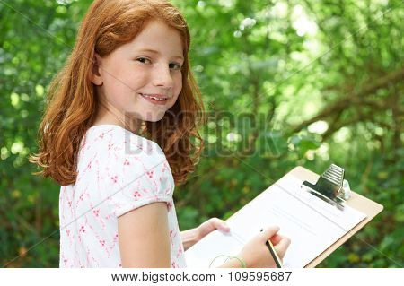 Girl Making Notes On School Nature Field Trip