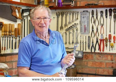 Senior Man In Workshop Standing With Tools