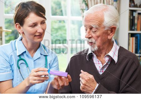 Nurse Advising Senior Man On Medication At Home