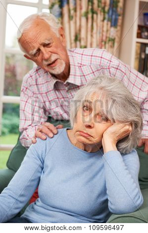 Senior Woman Suffering From Depression Comforted By Husband