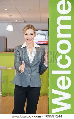 Businesswoman Welcoming Visitor To Office
