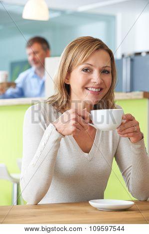 Portrait Of Woman Enjoying Hot Drink In Cafe