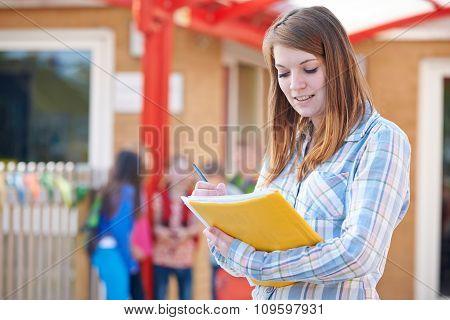 School Teacher Making Notes In Playground