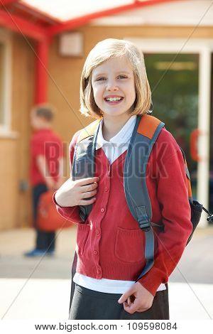 Girl Wearing School Uniform Standing In Playground