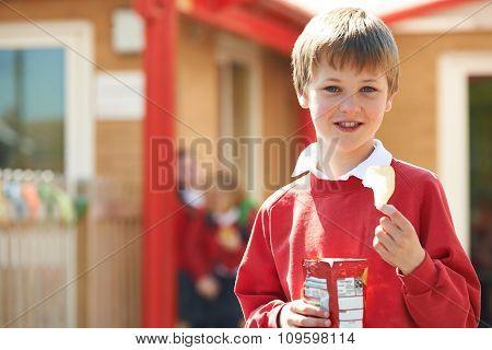Boy In School Uniform Eating Potato Chip In Playground