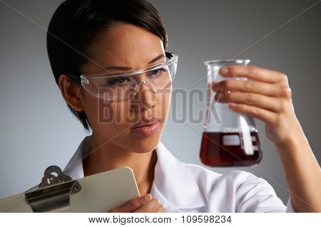 Scientist Holding Clipboard And Examining Beaker