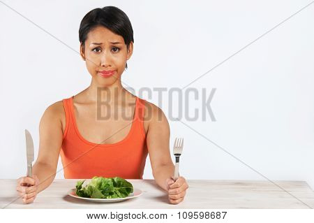 Unhappy Woman Sitting In Front Of Lettuce Leaves On Plate