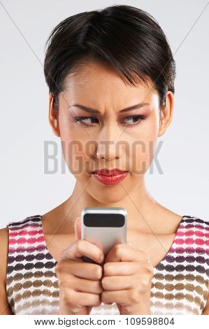 Young Woman Reading Text Message With Annoyed Expression