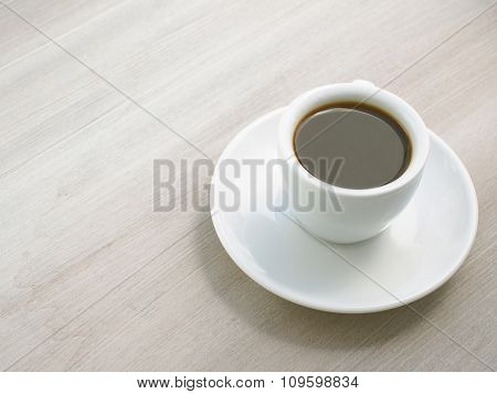 Espresso coffee in white cup on wooden table