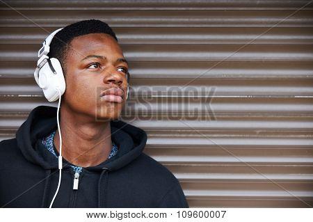 Teenage Boy Listening To Music In Urban Setting